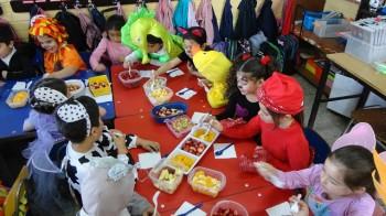 """Los niños disfrazados disfrutando de sus colaciones """"primaverales""""."""
